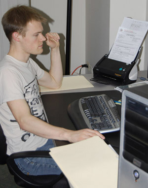 Planning + information specialist Ben Tatterton scans the cover sheet of a City development circulation for online access by BPG participants.