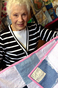 Norma Hunchak showing off a quilt